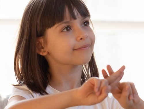 Young girl using sign language